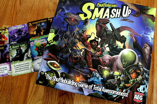 Box cover art and some cards from Smash Up by AEG.
